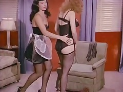 Betty Page and Lucy Kraven posing and wrestling