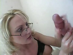 Dominating mistress with glasses stroking thick cock