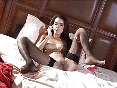 Glamour girl using dildo in bed
