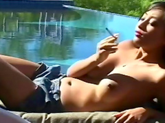 Smoking girl shows her big tits outdoors