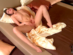 Teen in satin sheets masturbates pussy