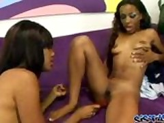 Two ebony babes play with a pink dildo