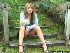 Cute blonde is smoking a cigarette in the garden
