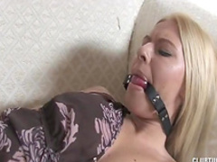Blonde with gag in mouth gets cum on her face