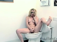 Curly blonde is fucking her puss with dildo in the toilet