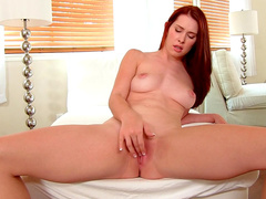 Big-titted redhead babe Melody Jordan plays with her puss