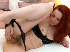 Redhead beauty Mystique plays with her pussy