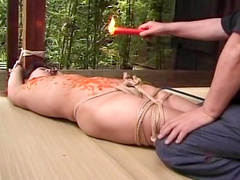 Babe with tied hands is getting hot wax