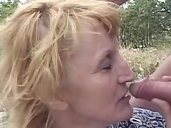 Blonde granny rides cock while sucking another outdoors