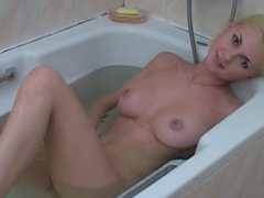 Blonde with big tits shows off her shaved pussy in the bath