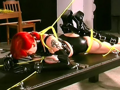 Sexy redhead in black latex tied up