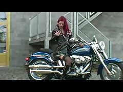 Red-haired biker in gripping striptease