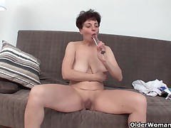 Breasty granny bonks herself with a glass sex-toy