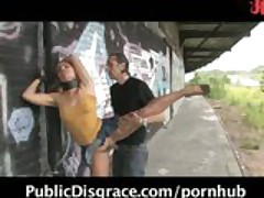 Flexible redhead is bound, stripped naked in public, and used by two men