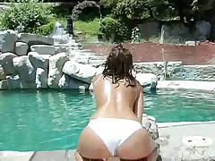 Smoking hot centerfold doing poolside striptease