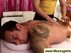Masseur rubs a guys tattoed body