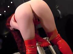 Redhead wearing red boots a corset and pantyhose