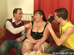 Fat mature babe takes two young cocks from both sides