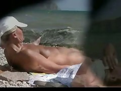 Watch a naked chick at the beach tan her hot body