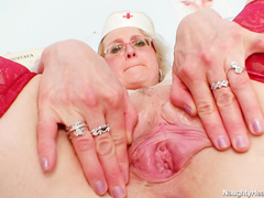 Mature blonde nurse Mora stretching her pussy
