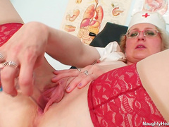Mature blonde nurse Mora stretching her pussy