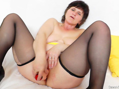 Granny stretches her holes with a dildo