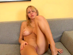 Cute blonde Stacy is lying and stroking her puss