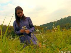Teen beauty in a grass field of flowers