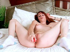 Redhead Emilie is poking her shaved pussy