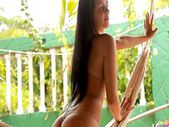 Dark-haired babe shows her shaved pussy