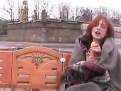 Redhead model is sucking her dildo outdoors