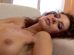 Curly brunette Leanna Sweet rubs her shaved pussy