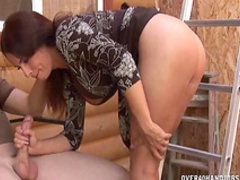 Brunette with big boobs is wanking a cock