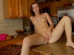 Sweet redhead Natalie Lust is sitting on the dildo