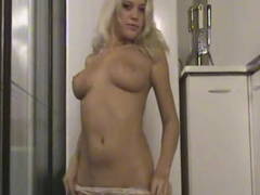 Young blonde strips at the kitchen showing her natural tits