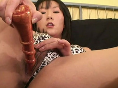 Sexy Asian babe pokes her shaved puss with red toy