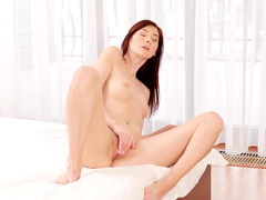 Slender redhead Kattie is masturbating her snatch