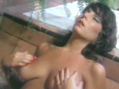 Curly-haired brunette is fingering her bald pussy
