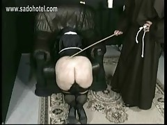 Naughty nun with her skirt up is kneeling for master priest and got spanked with a wooden stick