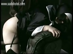 Dirty nun is kneeling on a chair and got spanked with wooden stick on her ass